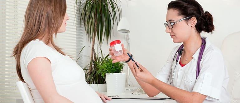 Врач дает беременной девушки баночку для анализа мочи